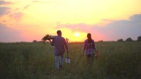 年轻愉快的种田的夫妇运载的箱、篮子充分产物有机蔬菜在他们的农场的日落的或日出 影视素材