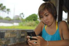 年轻愉快的美丽和甜亚裔妇女在咖啡店使用互联网app坐放松的手机微笑户外 免版税库存图片