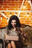 年轻愉快的美丽的妇女画象在金黄礼服藏品 免版税图库摄影