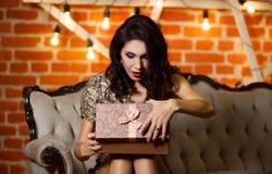 年轻愉快的美丽的妇女画象在金黄礼服藏品 免版税库存图片