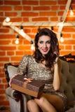年轻愉快的美丽的妇女画象在金黄礼服藏品 免版税库存照片