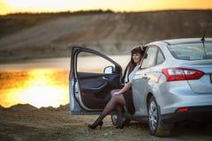 年轻愉快的美好的大大小式样女孩坐在她的汽车在日落在河附近 休息在一辛苦的工作以后的女商人 免版税图库摄影