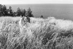 年轻愉快的美好的夫妇画象在自然的与大湖 拥抱在河或海银行的年轻夫妇  免版税库存照片
