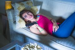 年轻愉快的西班牙拉丁吃玉米花的妇女沙发长沙发观看的电视在享受单独电视喜剧m的晚上在家放松了 库存照片