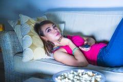 年轻愉快的西班牙拉丁吃玉米花的妇女沙发长沙发观看的电视在享受单独电视喜剧m的晚上在家放松了 免版税图库摄影