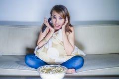 年轻愉快的西班牙拉丁吃玉米花的妇女沙发长沙发观看的电视在家放松了快乐的享用的单独滑稽的电视co 图库摄影