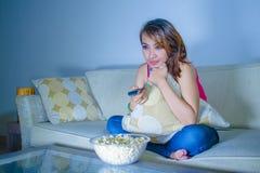 年轻愉快的西班牙拉丁吃玉米花的妇女沙发长沙发观看的电视在家放松了快乐的享用的单独滑稽的电视co 库存图片