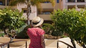 年轻愉快的跟随她的妇女邀请的人与她的戴红色礼服、太阳镜和帽子的手 在游泳场的桥梁 股票视频