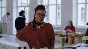 年轻愉快的非洲镜片的微笑销售专业的女商人,成为的严肃摆在时髦办公室 股票录像