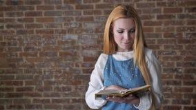 年轻感兴趣的白肤金发的女孩是阅读书,观看在照相机,微笑,砖背景 影视素材