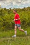 年轻成人人在领域跑在夏令时 免版税库存照片