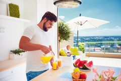年轻成人人,倒新鲜的汁液的父亲,当站立在露天场所厨房里在一个晴朗的夏日时 免版税库存照片