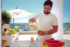 年轻成人人,倾倒在露天场所厨房之上的父亲新鲜的汁液晴朗的夏日 库存照片