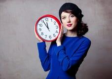 年轻成人女孩画象有大时钟的 库存照片