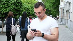 年轻成功的人使用在街道上的一个手机 影视素材