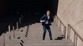 年轻成功的商人留给办公楼一个签的合同 他是在的愉快和滑稽的跳舞 股票录像