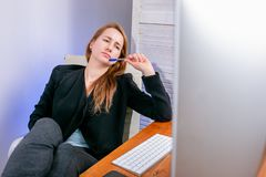 年轻成功的女实业家画象在办公室 她坐在桌上并且疲乏看显示器 休息,地方教育局 免版税库存图片