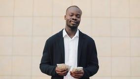 年轻成功的非裔美国人的商人在街道站立并且计数金钱 成功的商业 股票录像