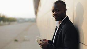 年轻成功的非裔美国人的商人在街道站立并且计数金钱 调查的他 股票视频