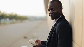 年轻成功的非裔美国人的商人在街道站立并且计数金钱 调查的他 影视素材