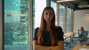 年轻成功的redhair女实业家身分画象在看照相机的办公室大厅里 股票录像