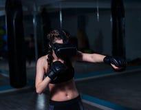 年轻戴着拳击手套的VR玻璃的战斗机拳击手适合的女孩 库存照片