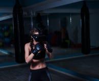 年轻戴着拳击手套的VR玻璃的战斗机拳击手适合的女孩 免版税库存图片