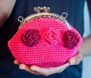 年轻手拿着有在c做的紫红色的花的小桃红色钱包 库存图片