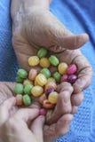 年轻手采摘从一个老人的棕榈的一块硬糖 免版税图库摄影