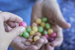 年轻手采摘从一个老人的棕榈的一块硬糖 免版税库存图片