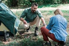 年轻投一个帐篷的人和妇女在森林 免版税库存图片