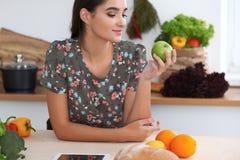 年轻拉丁妇女尖酸的绿色苹果 主妇在厨房里发现了烹调食物的一份新的食谱 库存图片