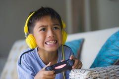 年轻拉丁小孩在网上激动的和愉快的使用的电子游戏与拿着控制器的耳机获得乐趣坐couc 库存照片