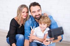 年轻拍与巧妙的电话的父母和小儿子照片在se 免版税库存图片