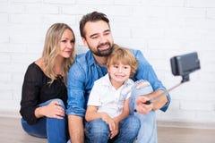 年轻拍selfie照片的父母和小儿子 免版税库存图片
