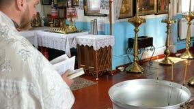 年轻教士在一个教会里读从圣经的一个祷告并且举办一个宗教仪式在乌克兰 影视素材