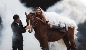 年轻新婚佳偶夫妇,时尚白色新娘婚礼服装骑马的美丽的秀丽新娘在强肌肉马待命 图库摄影