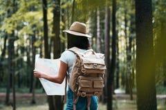 年轻旅客妇女举行定位图在树中的手在森林里和搜寻上定向旅行 库存图片