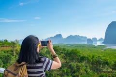 年轻旅客妇女背包徒步旅行者用途手机拍照片  图库摄影