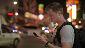 年轻旅游人背包徒步旅行者等待,当使用电话和叫出租汽车在唐人街在晚上时 影视素材