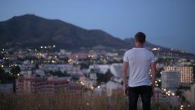 年轻旅游人背面图有胳膊的被举在小山顶部在晚上 股票视频
