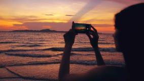 年轻旅游妇女剪影拍摄与智能手机的海景在日落期间在海滩 库存照片