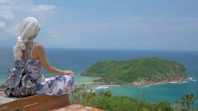 年轻旅游妇女坐在美好的海海湾风景观点  影视素材