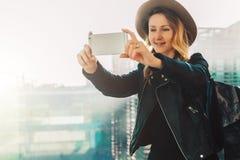 年轻旅游妇女帽子的和有背包的在机场站立并且拍照片,拍摄在智能手机` s照相机的录影 库存图片
