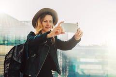 年轻旅游妇女帽子的和有背包的在机场站立并且拍照片,拍摄在智能手机` s照相机的录影 免版税库存图片