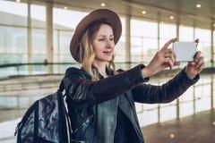 年轻旅游妇女帽子的和有背包的在机场站立并且拍照片,拍摄在智能手机` s照相机的录影 图库摄影