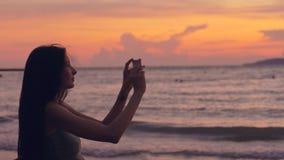 年轻旅游妇女拍摄与智能手机的海景在日落期间在海滩 库存照片