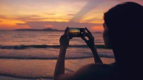 年轻旅游妇女特写镜头拍摄与智能手机的海景在日落期间在海滩 库存照片