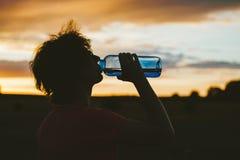 年轻旅游妇女饮用水的剪影的画象从一个透明蓝色瓶的在领域,在日落的瓶子 美国兵 免版税库存图片