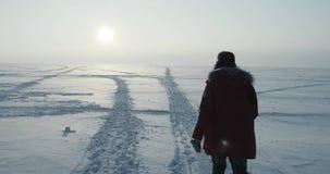 年轻旅行家通过飞雪努力去做在美好的日落 极性的远征 股票录像
